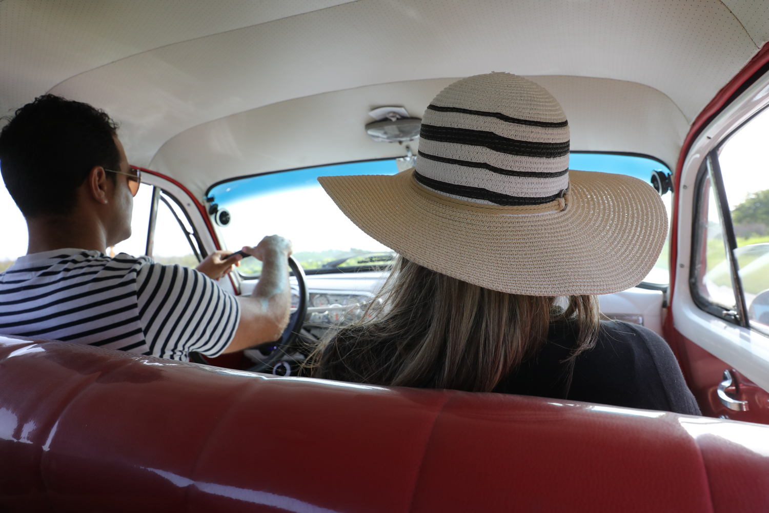 A Cuban couple driving the countryside in a classic car. - Cuba Photography